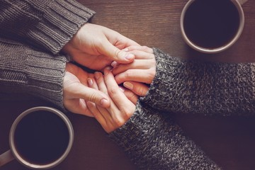 couple holding hands over coffee at table