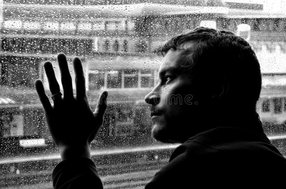 Man with a mood disorder with hand on glass window image