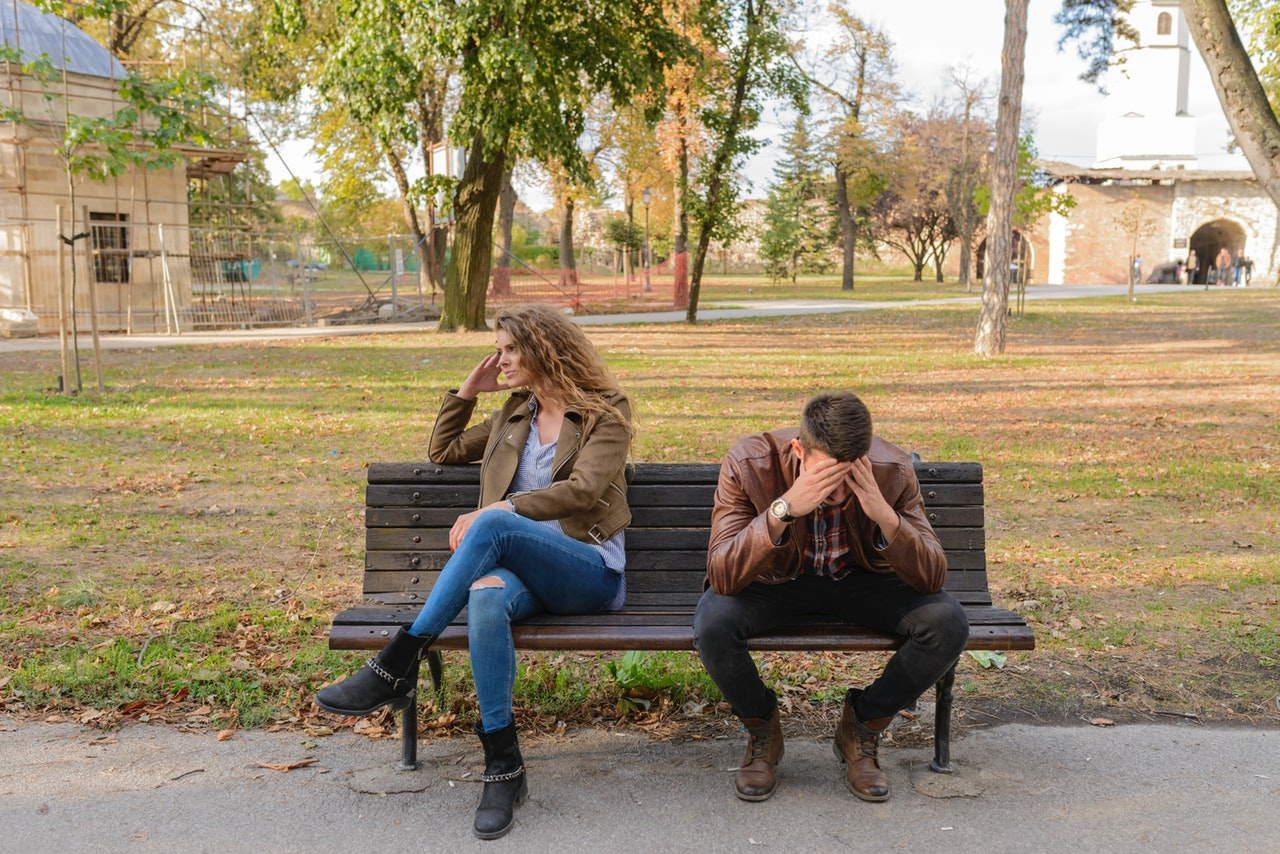 fighting couple sitting on park bench that are not in a collaborative divorce