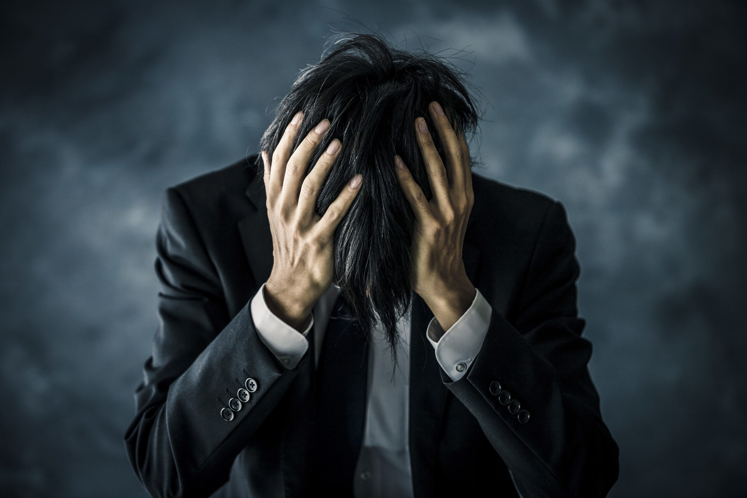 Image of Man Grabing his head with both hands